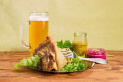 Baked ham hock, condiments and lager beer Royalty Free Stock Photo