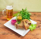 Baked ham hock on square white dish and lager beer Royalty Free Stock Photography