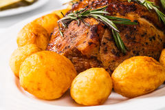 Baked Ham and Potatoes. Baked ham with rosemary and spices with oven roasted golden brown whole potatoes royalty free stock image