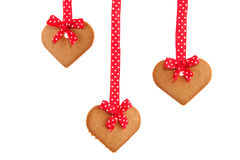 Baked hanging gingerbread hearts. With red speckles bows and ribbon Stock Image