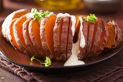 Baked hasselback potatoes with sour cream Royalty Free Stock Photo