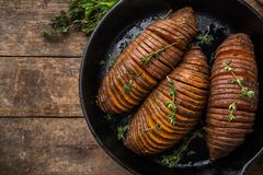 Baked hasselback sweet potato on cast iron pan. wooden backgroun Royalty Free Stock Photo
