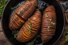 Baked hasselback sweet potato on cast iron pan. wooden backgroun Royalty Free Stock Photos