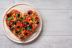Baked heart-shaped homemade pizza on a cutting board on white wooden background. Stock Photo
