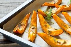 Baked hokkaido pumpkin in pieces on a baking tray Stock Photos