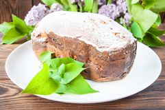 Baked homemade cake dusted with powder stands on a white plate near the lilac flowers. On a wooden background. royalty free stock photography