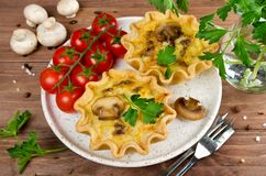 Baked homemade quiche pie in mini metal forms. Served with fresh greens, on a plate on old plank wooden background Stock Photos