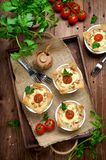 Ramekins with tasty chicken and bacon quiche on wooden board. Baked homemade quiche pie in ramekin served with fresh greens, on a dark wood tray on old plank