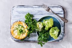 Baked quiche pie with greens. Baked homemade vegetable broccoli quiche pie in mini metal forms served with fresh greens, plate, fork on white serving board on Royalty Free Stock Images