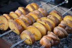 Baked hot potato with spices on skewers. Delicious baked hot potato with spices on skewers Royalty Free Stock Images