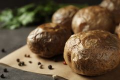 Baked jacket potatoes on grey table, closeup. Space for text royalty free stock photography
