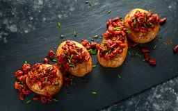 Baked jacket potatoes topped with red kedney beans in tomato sauce and chives served on stone board Stock Photos