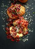 Baked jacket potatoes topped with red kedney beans in tomato sauce and chives served on stone board stock image