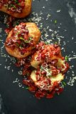 Baked jacket potatoes topped with red kedney beans in tomato sauce and chives served on stone board Royalty Free Stock Images