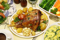 Baked Leg Of Lamb. Roasted leg of lamb with vegetables, mint jelly, gravy and spinach polenta stock photo