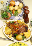 Baked Leg Of Lamb. Roasted leg of lamb with vegetables, mint jelly, gravy and spinach polenta royalty free stock image