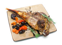 Baked leg of lamb with carrots, prunes and rosemary on a plate o Stock Photo