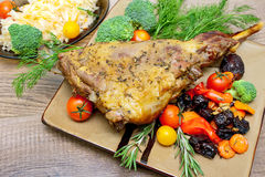 Baked leg of lamb with vegetables and herbs on a plate on a wood Royalty Free Stock Photo