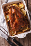 Baked lemon chicken with herbs in baking dish close up. vertical Stock Photo