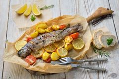 Baked lemon trout. With oven-roasted rosemary potatoes and tomatoes, served on baking paper fish soup served with fresh white bread royalty free stock photography