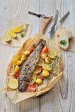 Baked lemon trout. With oven-roasted rosemary potatoes and tomatoes, served on baking paper fish soup served with fresh white bread stock photo
