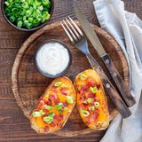 Baked loaded potato skins with cheddar cheese and bacon, garnish royalty free stock photo