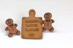 Baked with love. Close-up of gingerbread men and cutting board Royalty Free Stock Photo