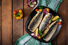 Baked mackerel with herbs. And garnished with lemon and pickled vegetables. Top view royalty free stock image
