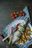 Baked mackerel with lemon and baked potatoes on a white plate. Fresh vegetables . Cherry, chili pepper. Cutlery. View from above. royalty free stock photos