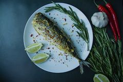 Baked mackerel served on a plate, decorated with spices, herbs and vegetables. Proper nutrition. View from above. Dark background royalty free stock images