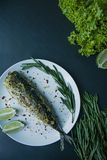 Baked mackerel served on a plate, decorated with spices, herbs and vegetables. Proper nutrition. View from above. Dark background stock photos