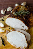 Baked meat with basil and garlic. On wooden board Royalty Free Stock Images