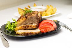 Baked Meat with Grilled Potato on white table. Baked Meat with Grilled Potato and Tomato on Served White table Stock Photos