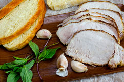 Baked meat with homemade bread. Basil and garlic on wooden board Royalty Free Stock Images