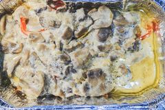 Baked meat with mushrooms in foil in the hot oven royalty free stock photography