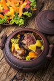 Beef stew in ceramic pot. Baked meat with orange sauce in a rustic ceramic pot Royalty Free Stock Image