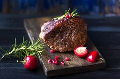Baked meat with rosemary and red pepper. steak. beef. dinner for men. dark photo. Black background. wooden board. royalty free stock image