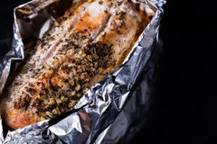 Baked meat with seasoning in foil on black tray. Baked pork meat with seasoning in foil on black tray Royalty Free Stock Photo