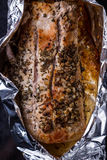Baked meat with seasoning in foil on black tray. Baked pork meat with seasoning in foil on black tray Stock Image