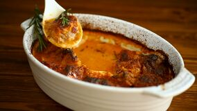 Baked meat with spices vegetables and gravy in a ceramic form