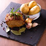 Baked meat with vegetble and herbs on slate stone. Square photo of baked piece of pork meat with green rosemary herb on the top. Color pepper, bay leaf, onion Stock Photos