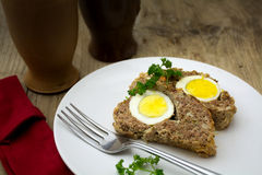 Baked meatloaf with boiled eggs for Easter on rustic wood Royalty Free Stock Image