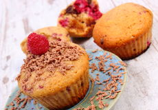 Baked muffins with raspberries and grated chocolate on wooden background, delicious dessert Royalty Free Stock Photos