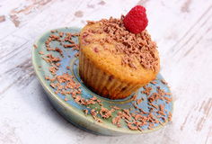 Baked muffins with raspberries and grated chocolate on wooden background, delicious dessert Stock Images
