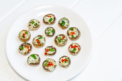 Baked muhrooms with blue cheese, red pepper and spring onion Stock Photo