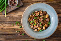 Baked mushrooms with soy sauce and herbs. Vegan food. Top view stock image