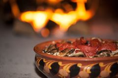 Tomatoes baked with mushrooms in a clay bowl with an ornament on the background of a wood-burning stove stock photography