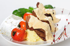 Baked mutton meat with creamy sauce, mashed potato and cherry tomatoes Royalty Free Stock Photos