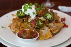 Baked nachos with sour cream, salsa,and pickled jalapenos Royalty Free Stock Photography