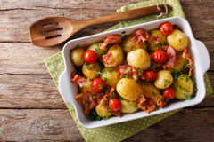 Baked new potatoes with bacon and tomatoes close-up in a baking Stock Image